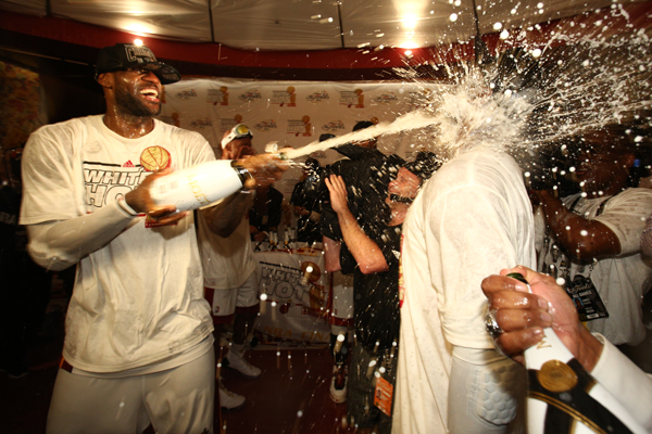 LeBron James (left) celebrated his second career championship with some champagne. (David Alvarez/Getty Images)