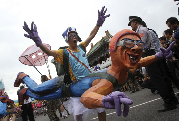 A man wears a papier-mache figure during the Dream Parade in Taipei, Taiwan on Saturday. (AP Photo/Chiang Ying-ying)