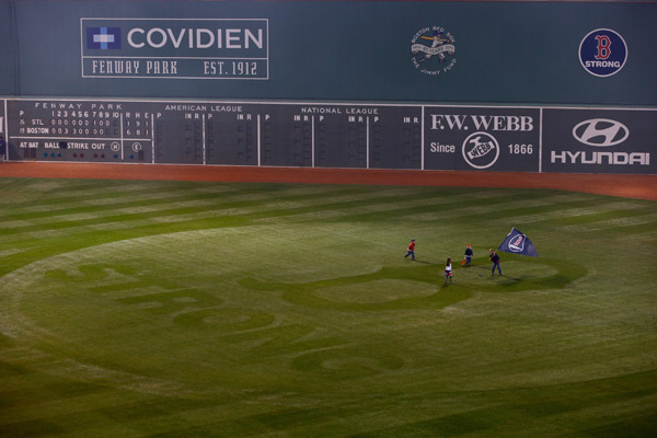 Young fans carry a flag on the field after Boston's Game 6 victory. (Jared Wickerham/Getty Images)