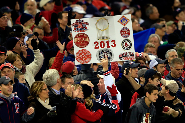A Red Sox fan holds a sign commemorating the team's eight championships. (Jamie Squire/Getty Images)