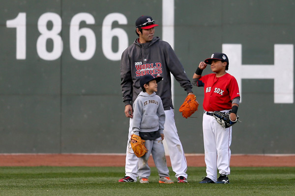 Koji Uehara stands on the field with his son Kaz and D'Angelo Ortiz before Game 6. (Rob Carr/Getty Images)