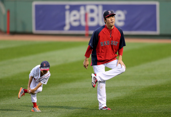 Koji Uehara warms up with his son Kazuma during Red Sox practice on Tuesday. (Rob Carr/Getty Images)