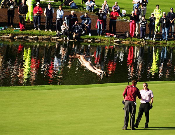 A streaker dives into the water by the 18th green as Paul McGinley (R) of Europe shakes hands with JJ Henry of the U.S. after they halved their match on the final day of the 2006 Ryder Cup.