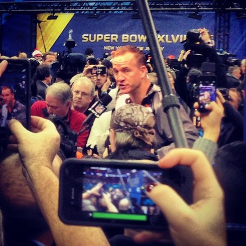 Manning in a sea of reporters. (themantz/instagram)