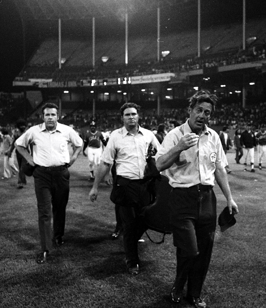 The umpires walk off the field after calling a forfeit. (Getty Images)
