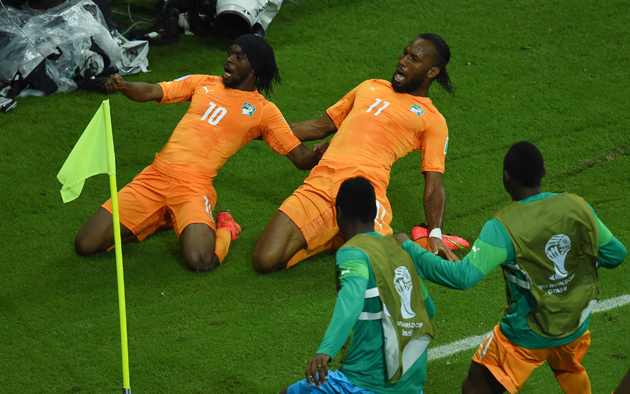 Gervinho, left, and Didier Drogba slide in unison toward the corner flag, where they are joined by their teammates after the former's game-winning goal in the Ivory Coast's 2-1 win over Japan.