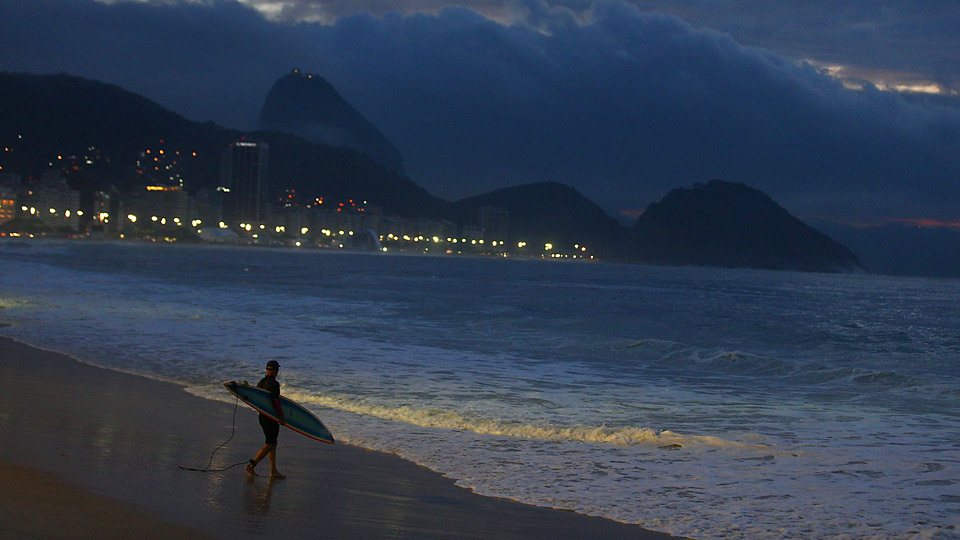 At nearly sunrise in the second week of the World Cup, a lone surfer walks toward the waves at a mostly empty Copacabana Beach.