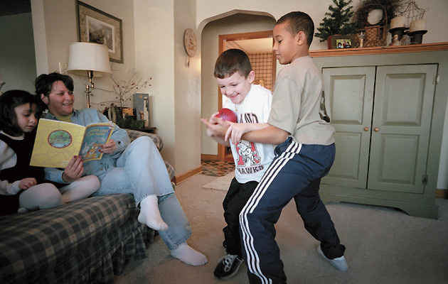 Jordan (right), adopted by the Millers, plays with his brother Cameron as sister McKenzie and mother Shelly look on.