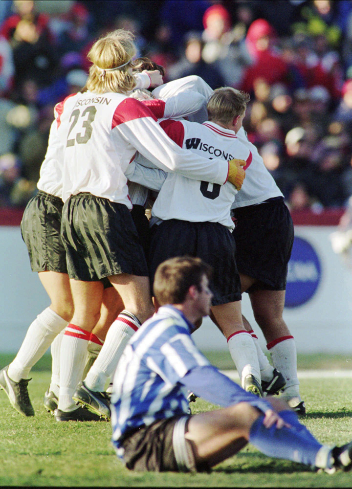 Wisconsin players celebrate their 2-0 1995 men's soccer national championship win over Duke, while Blue Devils' defender Sam Smith sits in dismay.