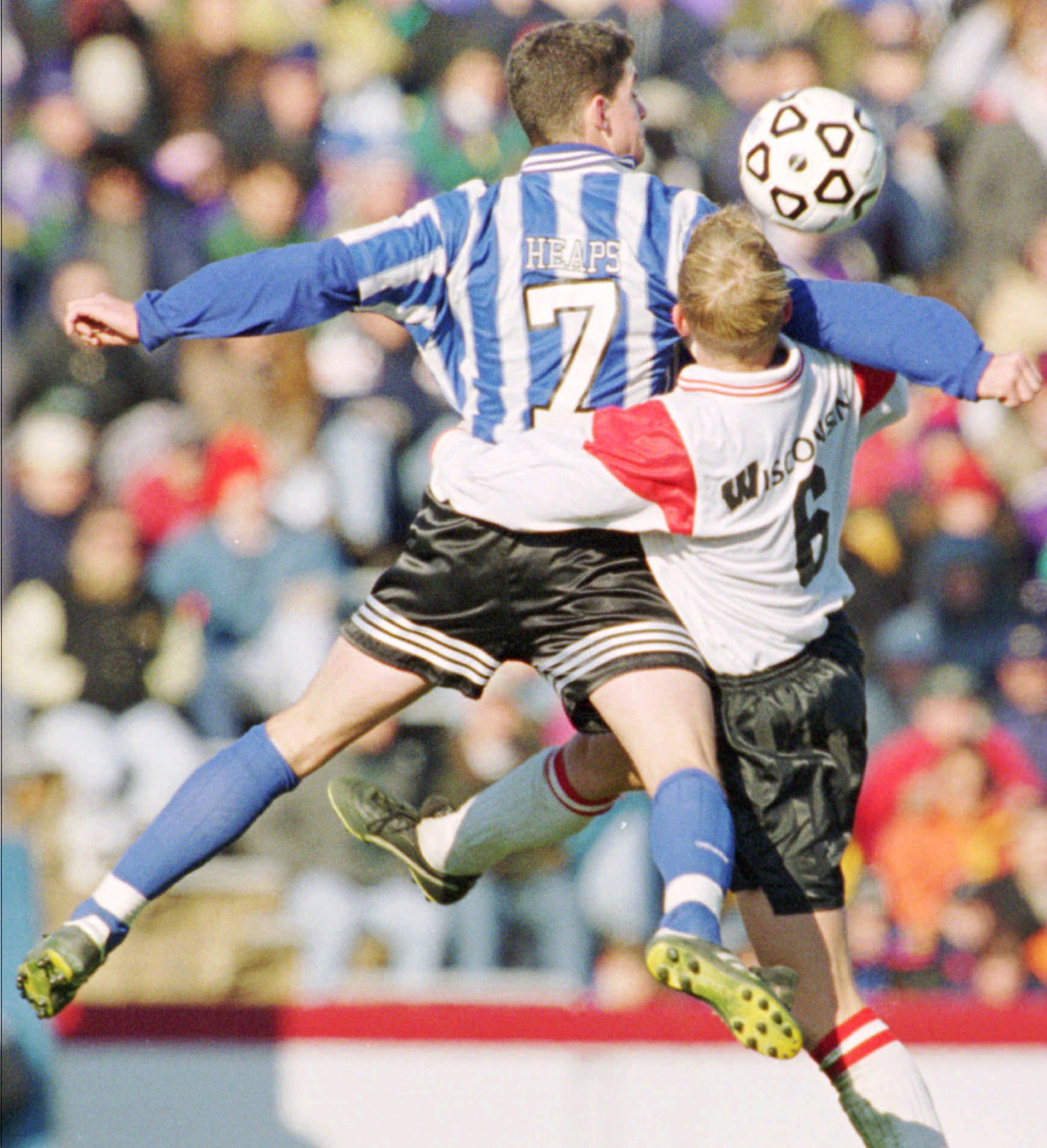 Current New England Revolution manager Jay Heaps leaps through the grab of Wisconsin midfielder Alastair Steel.