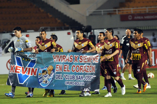 Players from Bolivian club San Jose carry a banner in remembrance of Kevin Espada, a fan who was killed by a thrown flare in a match against Brazil's Corinthians.