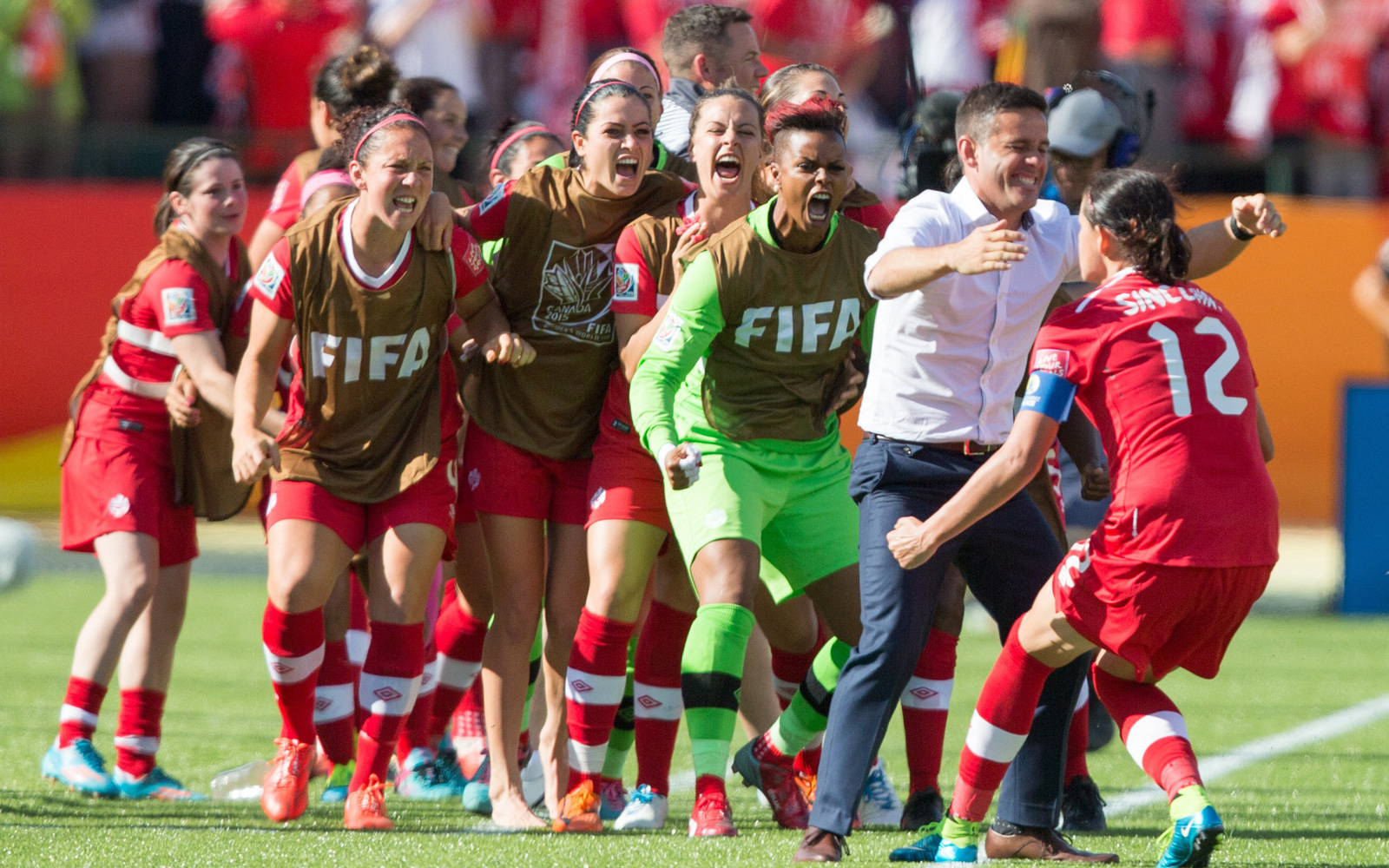 Christine Sinclair runs over to the bench, led by manager John Herdman, after giving Canada a 1-0 lead over China.