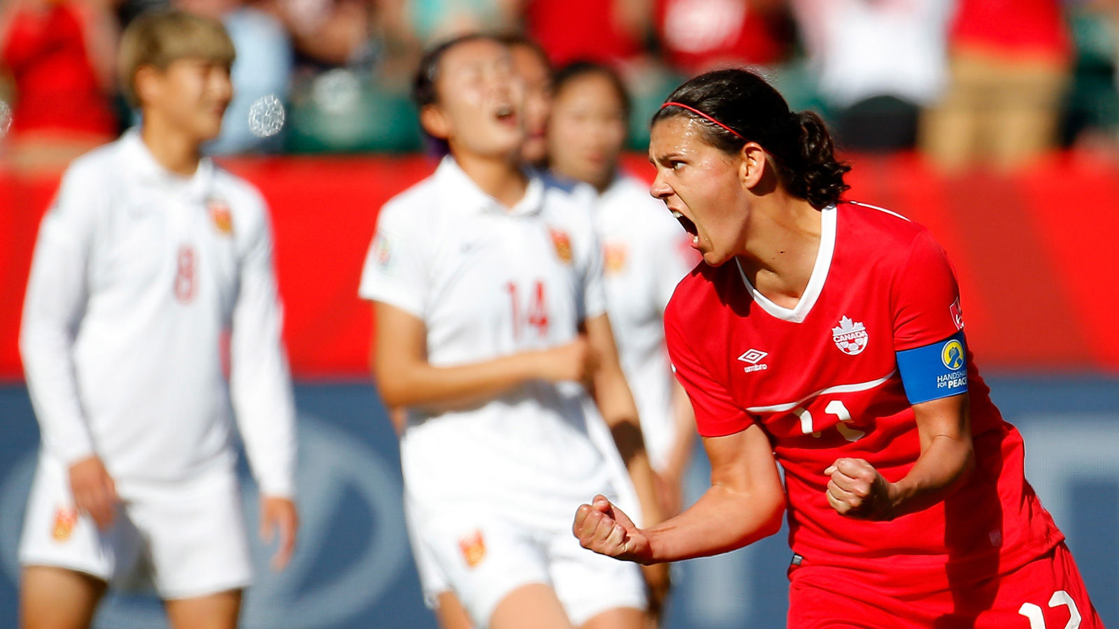 Christine Sinclair celebrates her converted penalty, to the dismay of her Chinese counterparts.