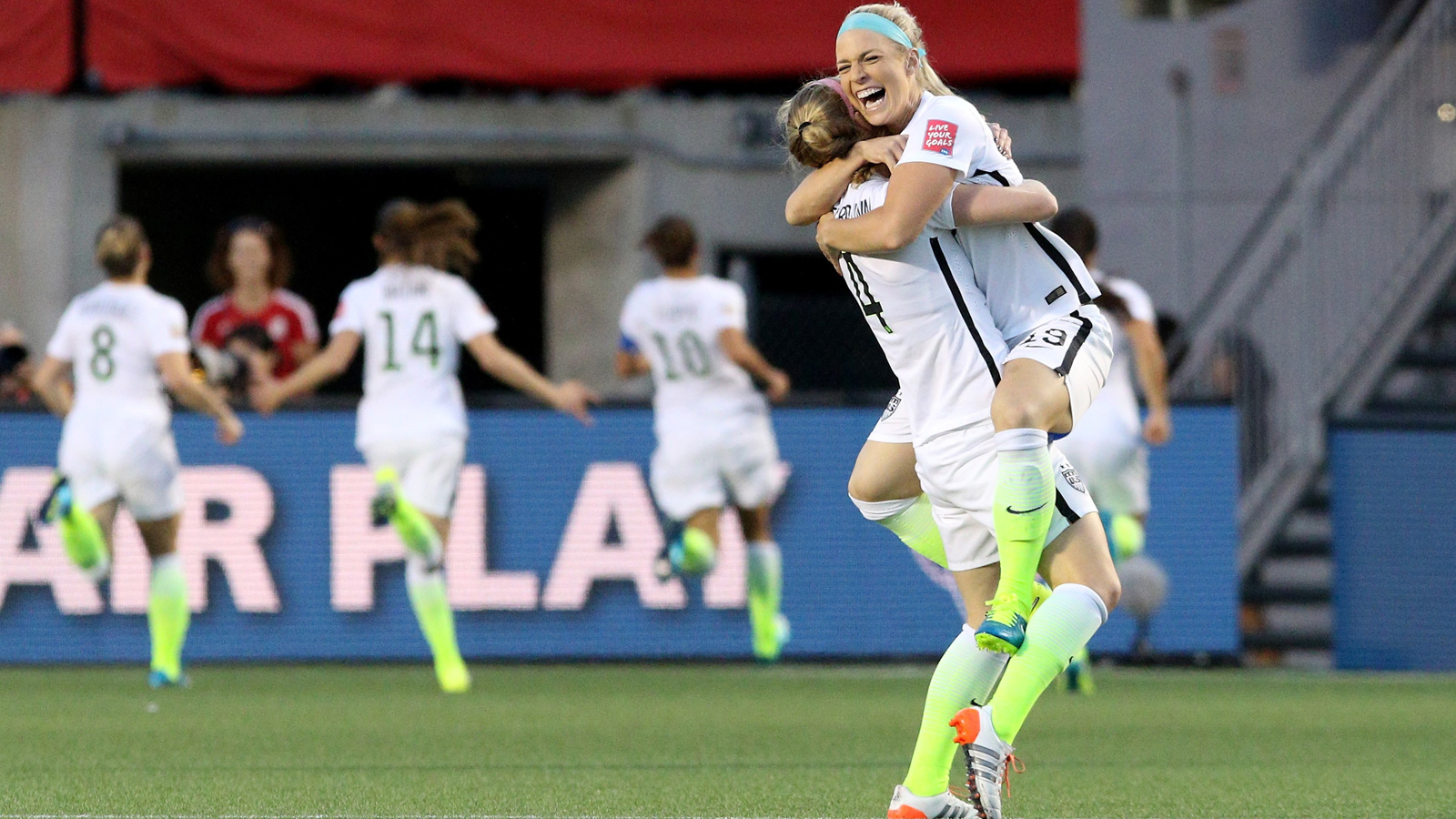 While Carli Lloyd (10) celebrates her goal in the distance, stalwart center backs Julie Johnston and Becky Sauerbrunn rejoice in the goal that put the USA into the semifinals of the Women's World Cup.