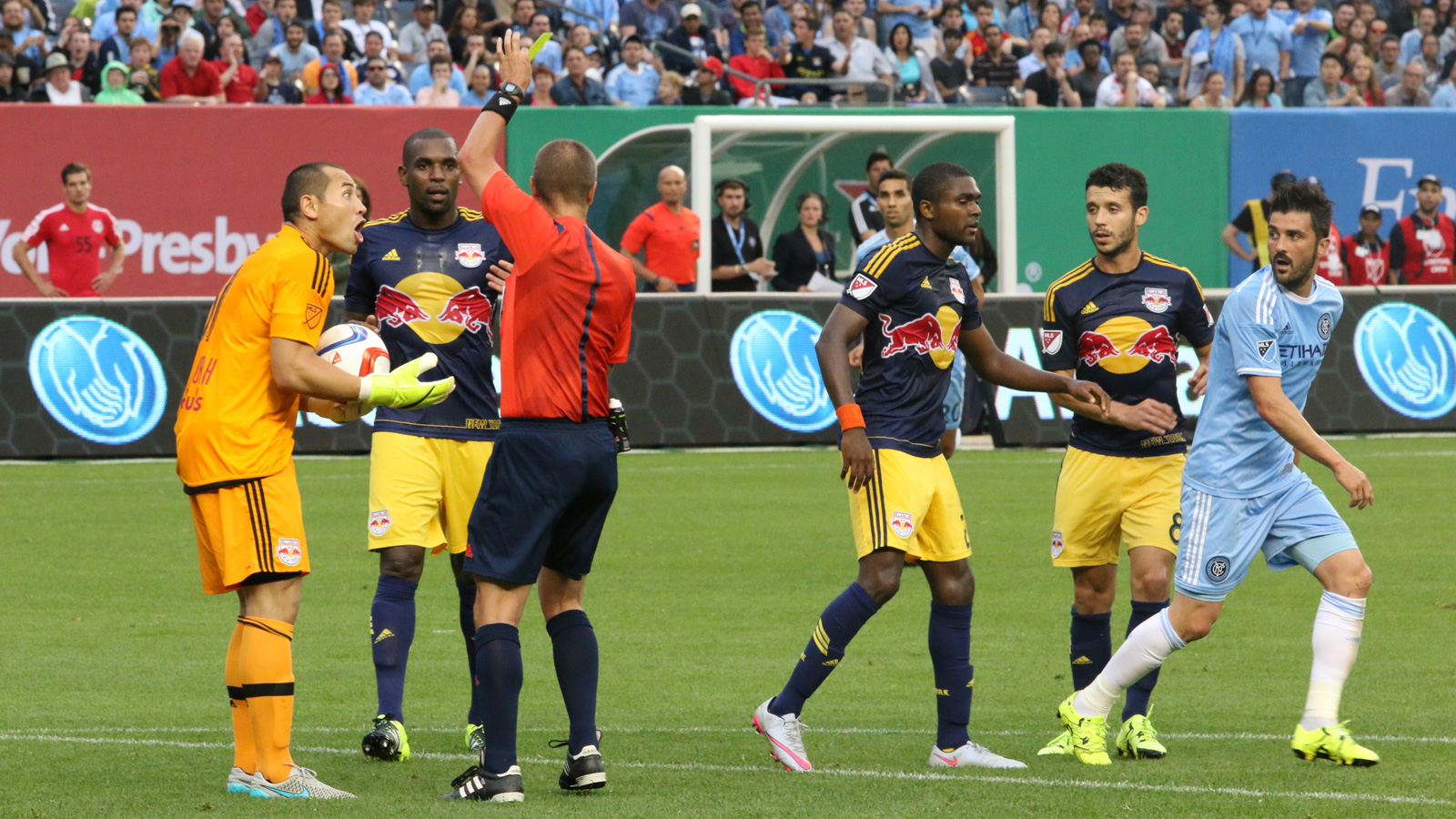 New York Red Bulls goalkeeper Luis Robles (right) reacts to receiving a yellow card for a foul on NYCFC striker David Villa (far right).
