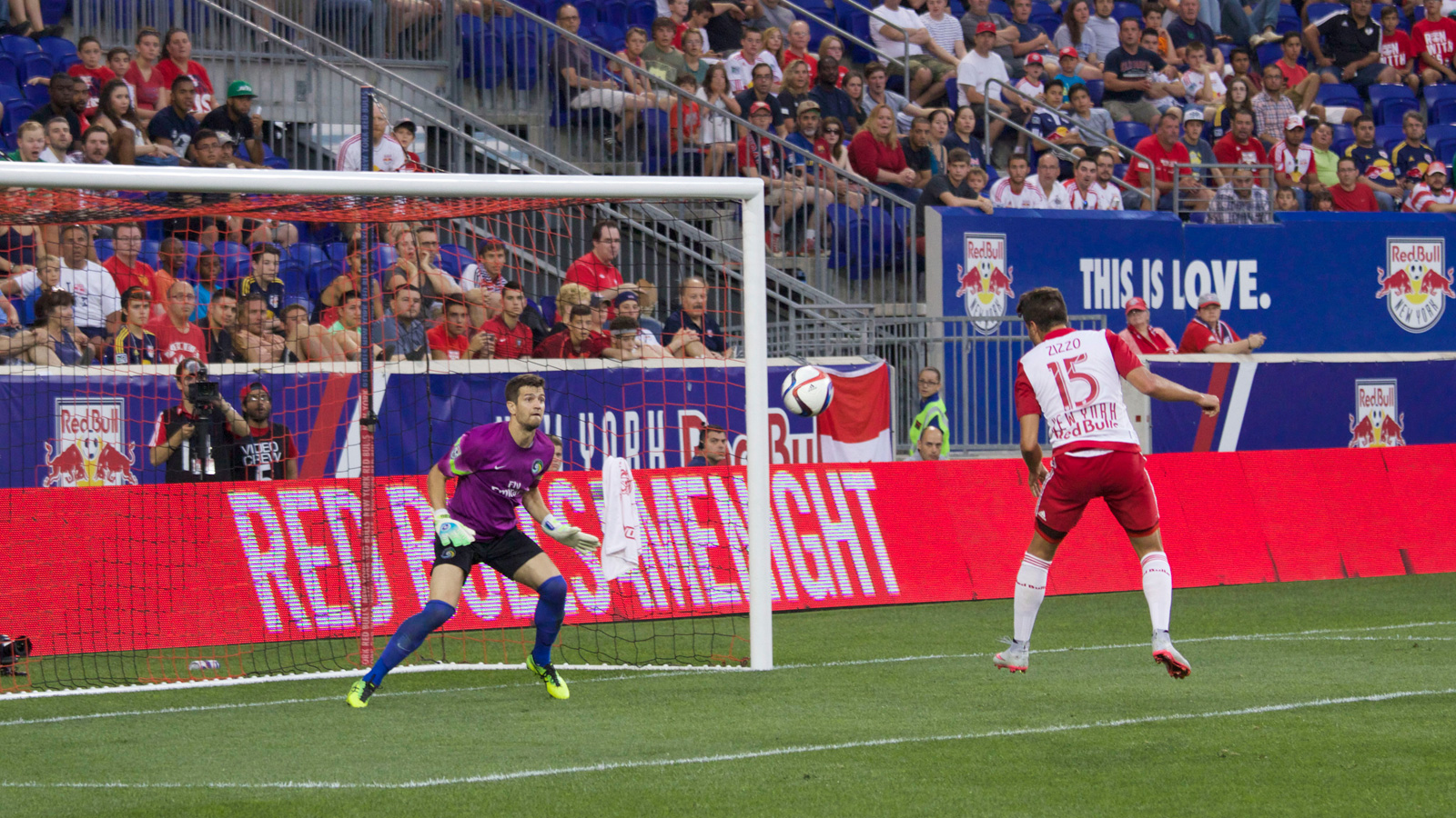 New York Red Bulls midfielder Sam Zizzo (15), already with a goal to his name in the match, fires a header toward Cosmos goalkeeper Jimmy Maurer (1).