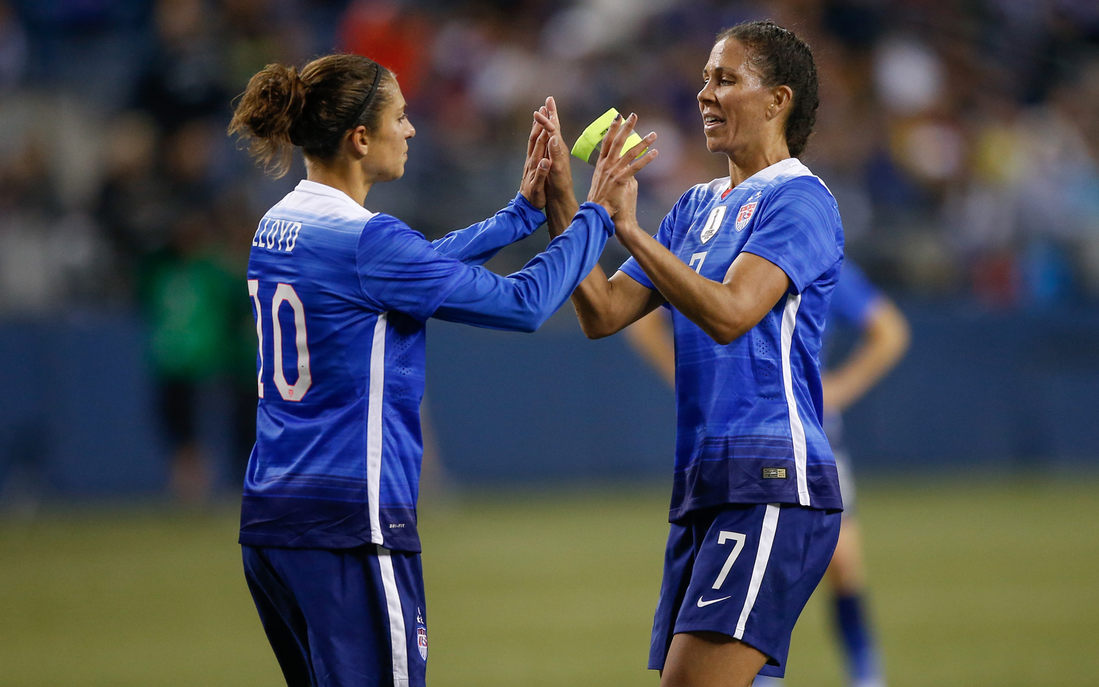 Shannon Boxx, right, passes off the captain's armband to Carli Lloyd in her final act as a player, riding into retirement in the first half of a 1-1 draw against Brazil in Seattle.