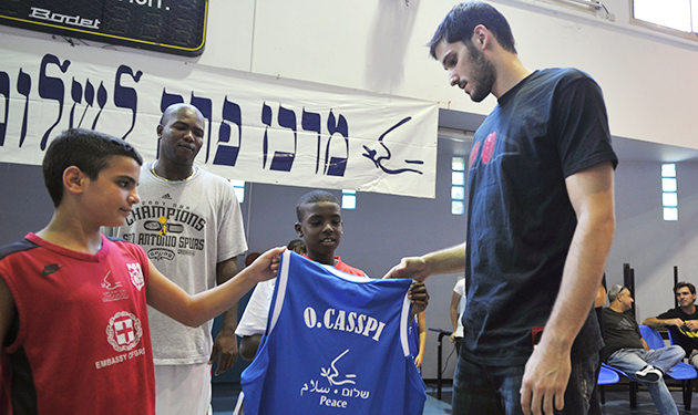 Omri Casspi, with a young Israeli (left) and Palestinian (right) in 2010, has given back to his home country.