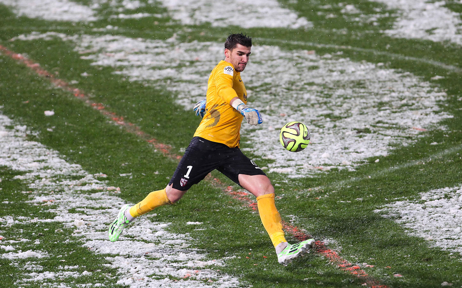A goalkeeper looks to plant on some snow-less ground in Metz's Ligue 1 game vs. Nice in January 2015.