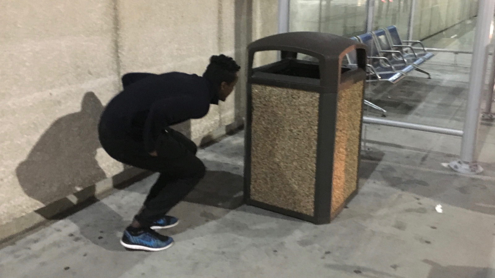 Saadiq Mohammed hides behind a trash can outside of Lambert-St. Louis International Airport, waiting to surprise Sa'ad Hussein upon his arrival to the USA.