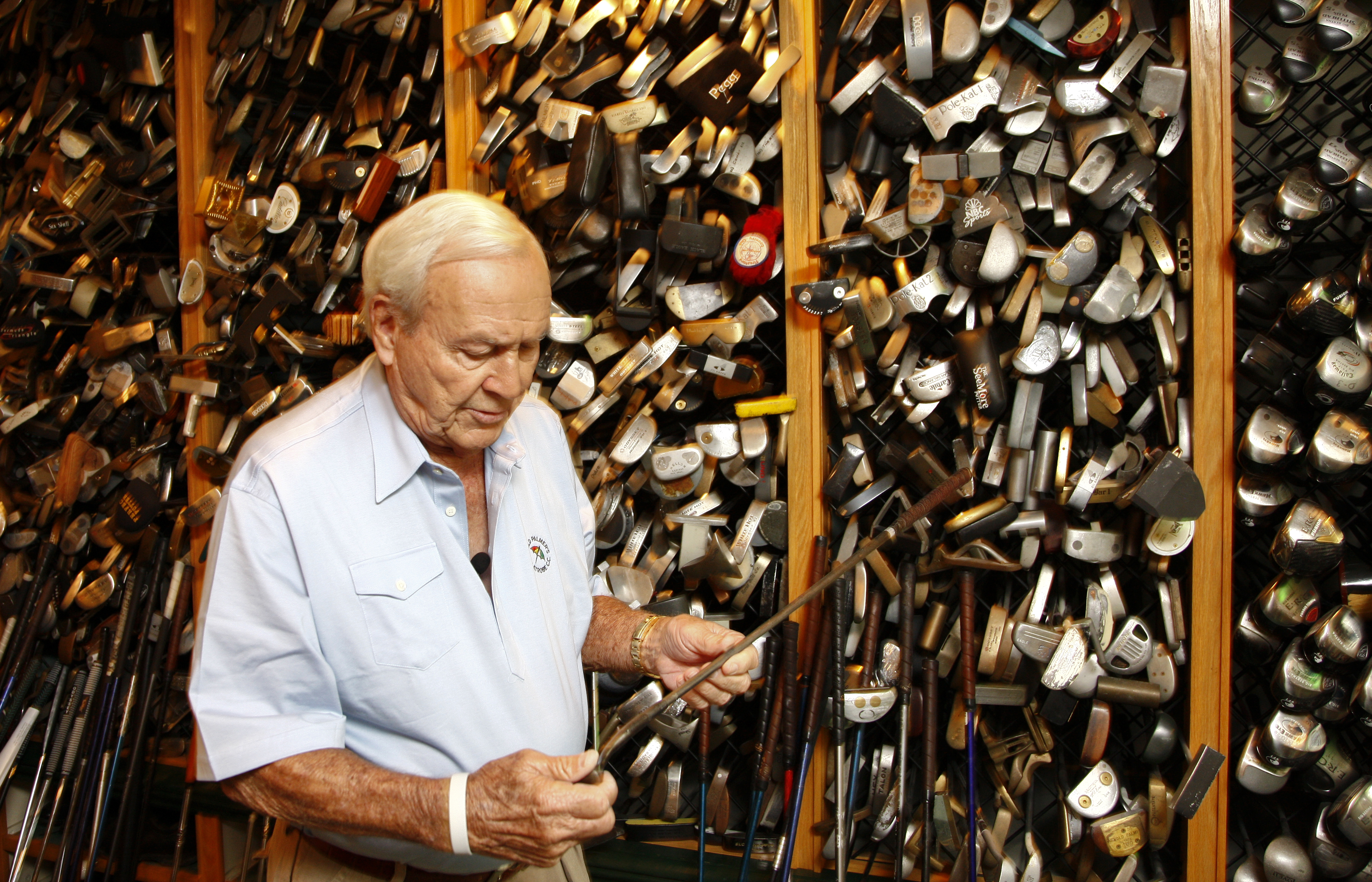 Arnold Palmer holds one of the thousands of clubs he collected over the years during a previous visit from Sports Illustrated.
