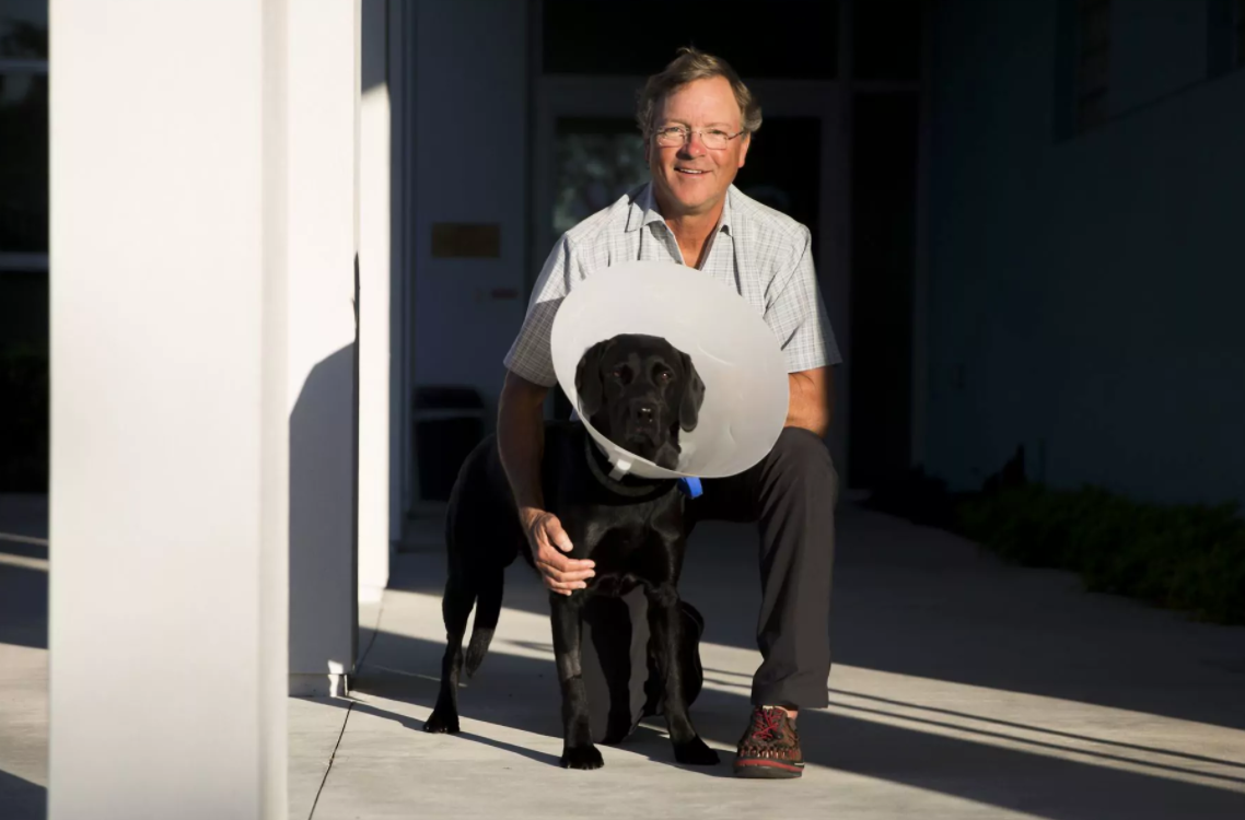 Daniel Copps with Carbon, a four-year old black lab who was bit by a gator.