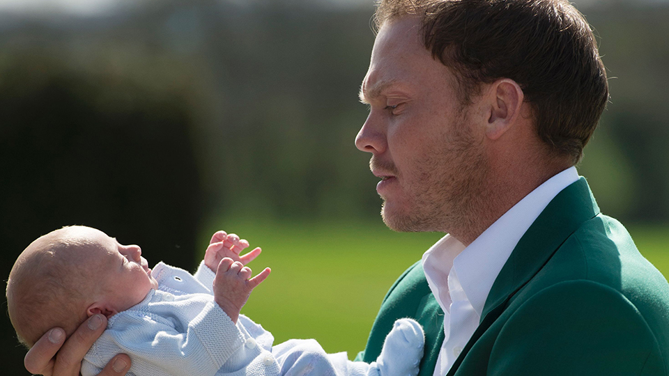 Danny Willett, wearing his Masters champion green jacket, holds his newborn son Zachariah James.