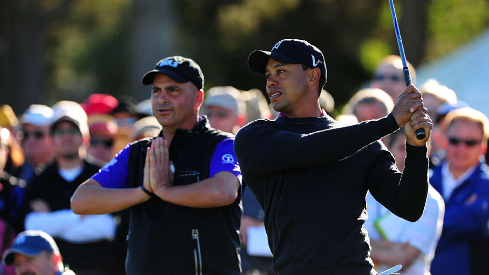 Rocco Mediate looks on as Tiger Woods swings during the first round of the 2011 Farmers Insurance Open.