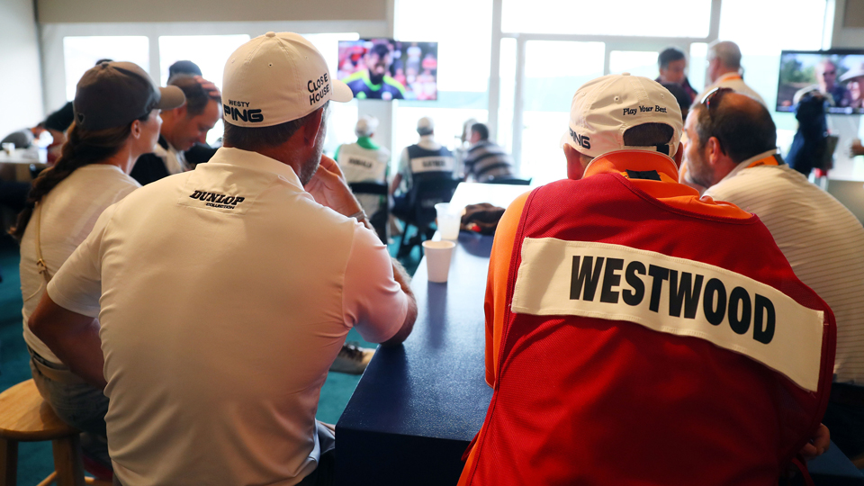 Lee Westwood and his caddie take a break during the rain delay.