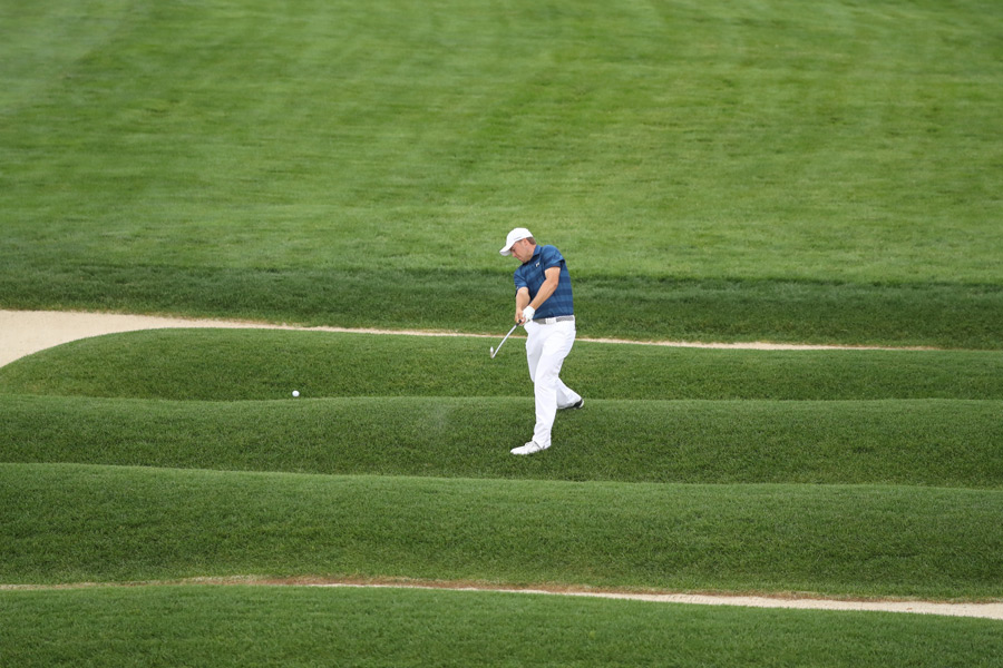 Defending champion Jordan Spieth hits out of the iconic church pew bunkers at Oakmont.