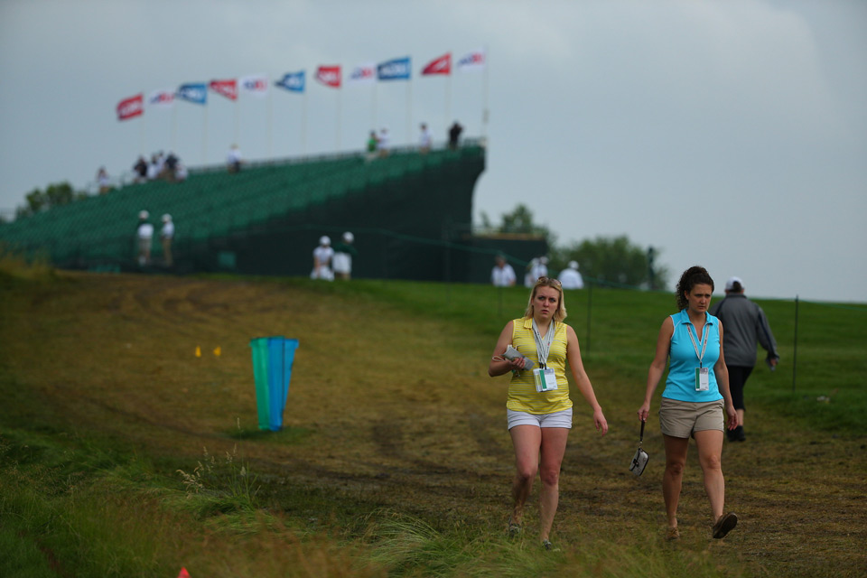Fans walk the muddy course Friday morning.