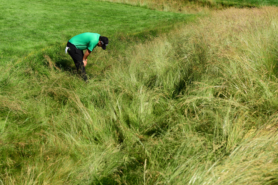 Patrick Reed searches through thick rough for his ball on Saturday.