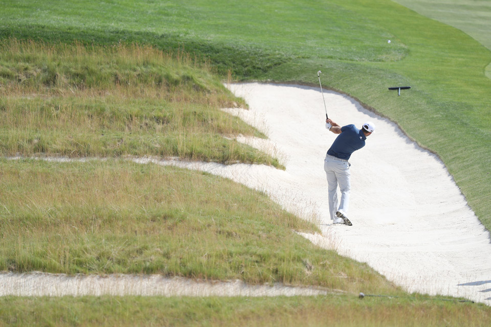 Dustin Johnson hits out of the iconic church pew bunkers during the final round.