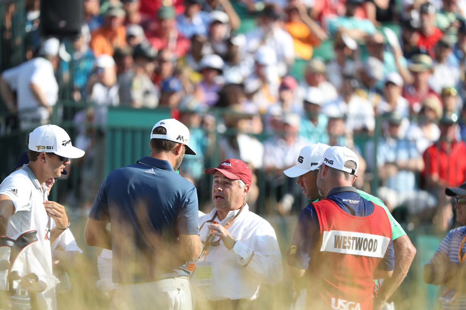 A rules official breaks the news to Dustin Johnson in the middle of the final round that he will be assessed a stroke penalty for an earlier infraction.