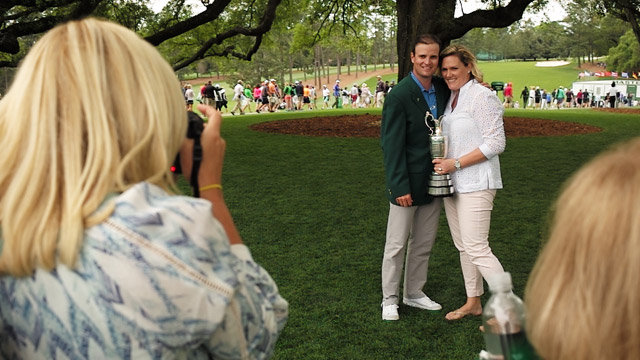 Zach Johnson with wife wearing green jacket and holding Claret Jug under oak tree at the 2016 Masters.