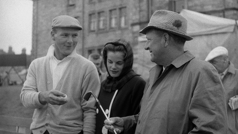 """Arnold Palmer chats with his wife Winnie and father, Milford """"Deke"""" Palmer at the first tee before starting second round play in the 1960 Open Championship at St. Andrews, Scotland."""