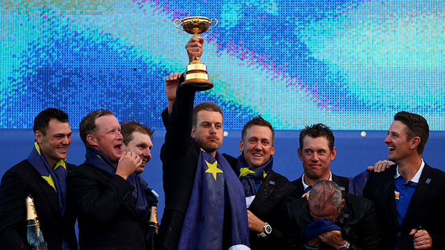 Henrik Stenson lifts the trophy as Europe team captain Paul McGinley celebrates winning the Ryder Cup with his team after the Singles Matches of the 2014 Ryder Cup.