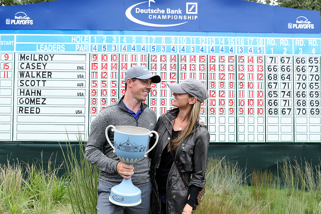 Rory McIlroy of Northern Ireland and fiancee Erica Stoll pose with the trophy during the final round of the Deutsche Bank Championship.