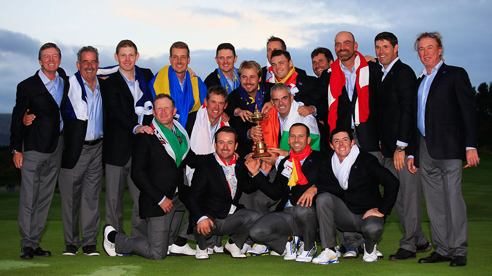 Team Europe, donning their respective countries' flags, pose with the Ryder Cup after a securing the 16 1/2 - 11 1/2 victory over the Americans.