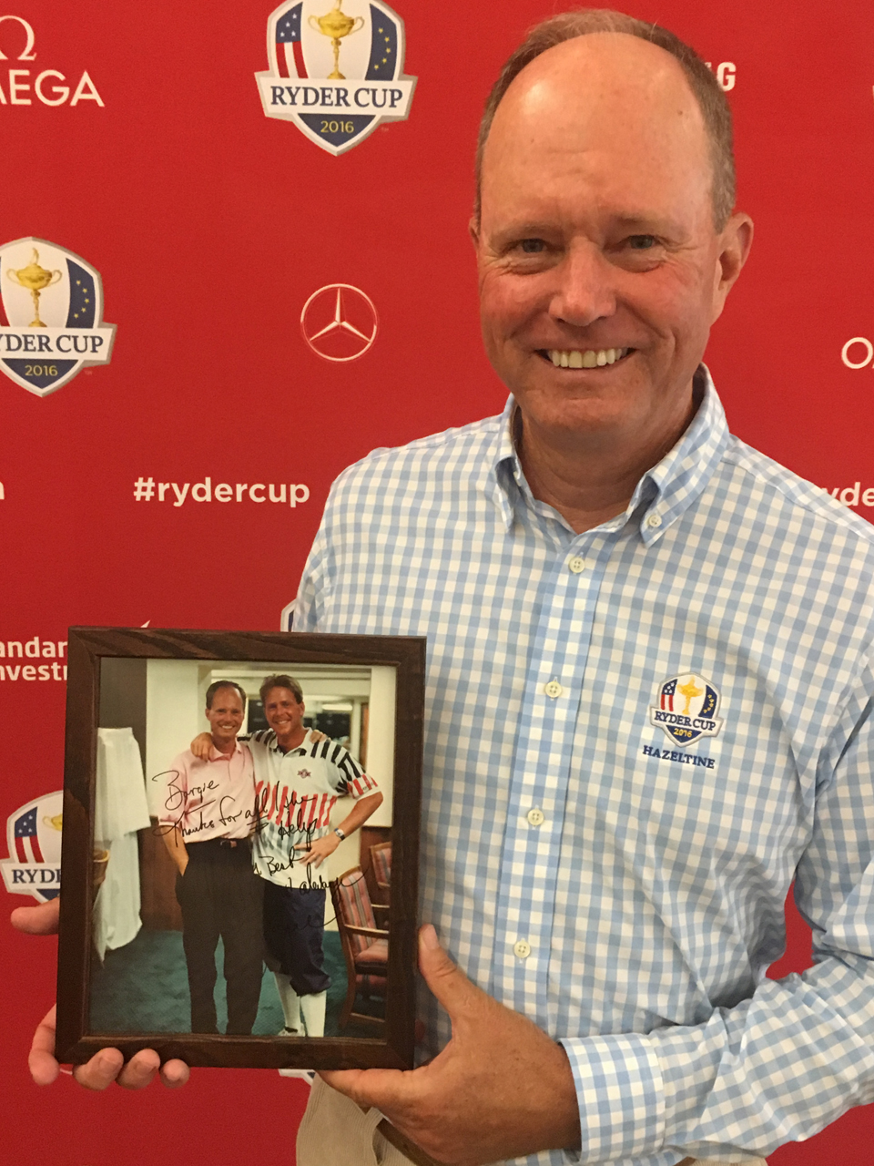 Mike Barge, the director of instruction at Hazeltine, holds up a photo of him and Stewart that they took together after the 1991 U.S. Open, which was autographed by Stewart years later. Barge and Stewart were college teammates at SMU.