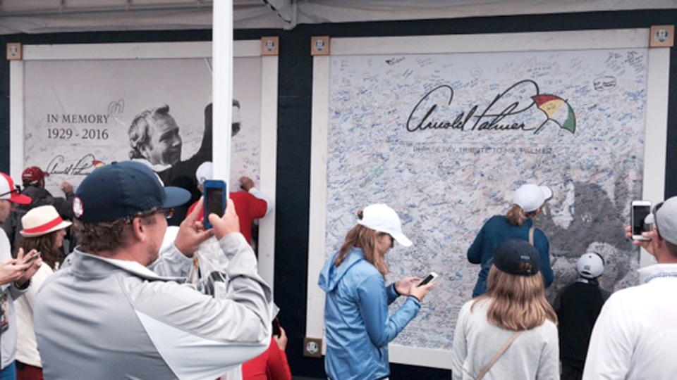 Fans take photos and sign the posters in honor of Arnie.