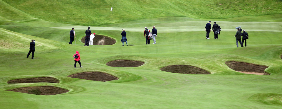 Donald Trump plays out of a bunker on the fourth after the opening of The Trump International Golf Links Course on July 10, 2012 in Balmedie, Scotland.