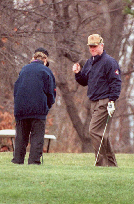 President Bill Clinton (R) talks to his wife Hillary as the two play a round of golf in Arlington, VA.