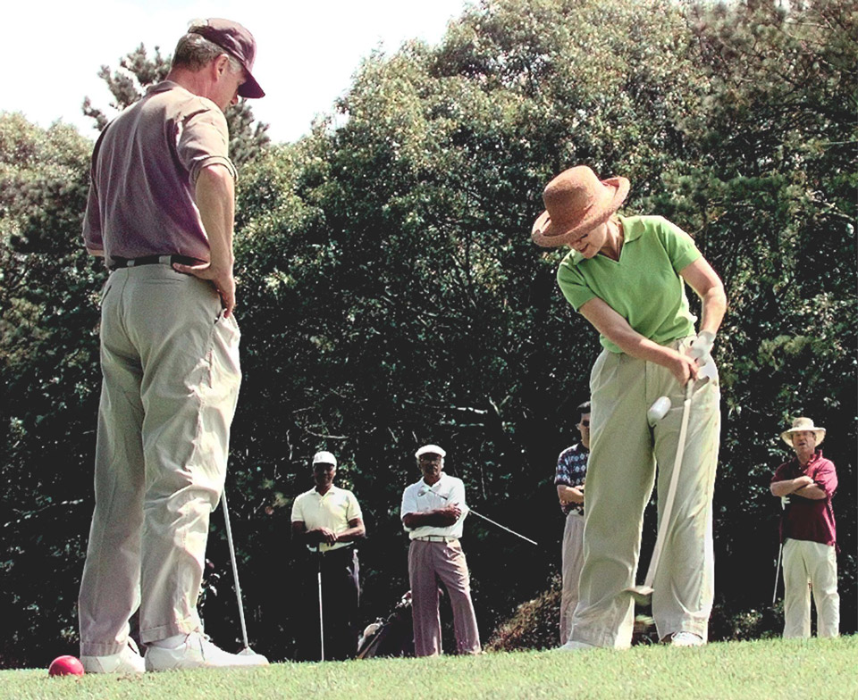 President Bill Clinton (L) watches First Lady Hillary Rodham Clinton (R) tee off on the first hole at Mink Meadows Golf Course on Martha's Vineyard, MA in August 1993.