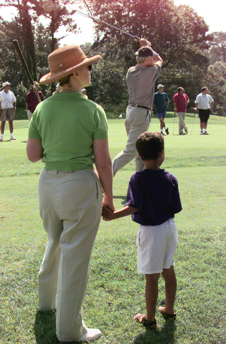President Bill Clinton tees off on the first hole as First Lady Hillary Rodham Clinton (L) and Mercer Cook (R), age 5, look on at Mink Meadows Golf Course on Martha's Vineyard, MA.
