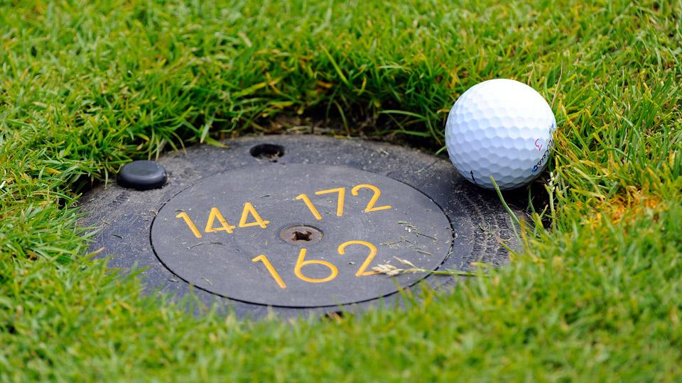 A golf ball rest on the edge of a sprinkler head.
