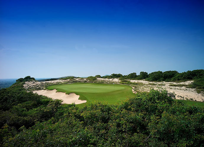 The 10th hole is a three-shot par 5 with a multilevel green nestled between a bunker and a waste area.