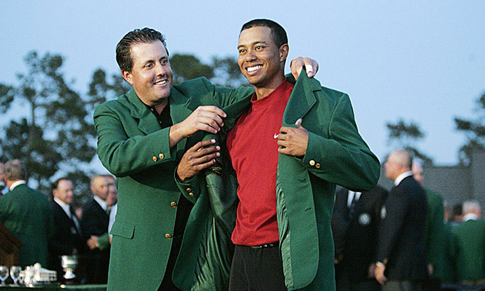 A year after winning his first major, Phil Mickelson presented Woods with the green jacket.