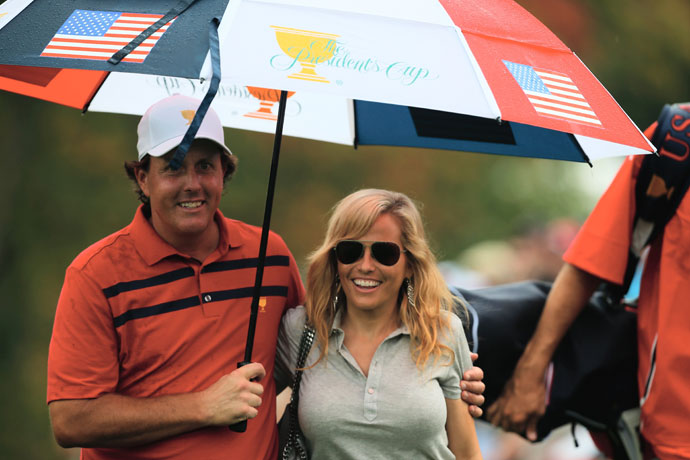 Phil Mickelson waits under an umbrella with Amy during the Day Three Four-ball Matches at the Muirfield Village Golf Club at the 2013 Presidents Cup.