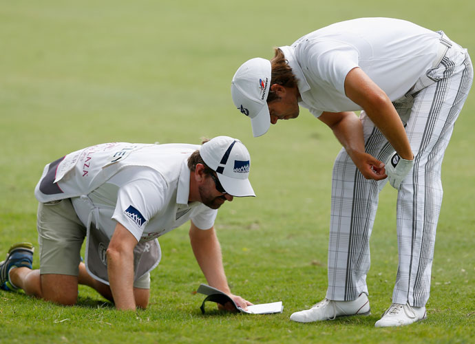 Aaron Baddeley and his caddie inspect Baddeley's ball on the seventh fairway. Baddeley got to within a shot of the lead before bogeying the 14th and 17th. He'll start the final round -4, three shots back of the lead.